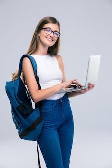 Ritratto di un'adolescente felice che usa il computer portatile isolato