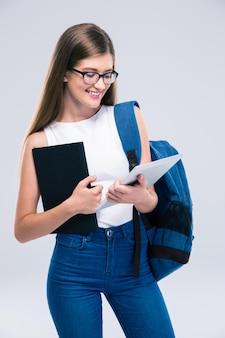 Ritratto di un'adolescente felice con zaino e libro utilizzando un computer tablet isolato su uno spazio bianco