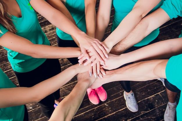 Ritratto di giovani amici femminili di misura felice che impilano le mani.