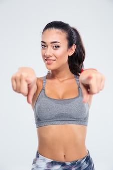 Ritratto di una donna felice fitness puntare il dito davanti isolato su un muro bianco