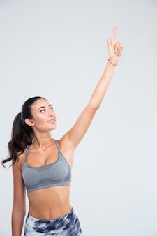 Ritratto di una donna felice fitness puntare il dito in alto isolato su un muro bianco