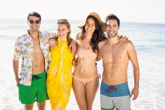 Ritratto di amici felici in piedi insieme sulla spiaggia