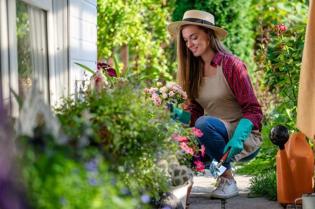 Il ritratto della donna di giardinaggio felice in guanti, cappello e piante del grembiule fiorisce sul letto di fiore in giardino domestico