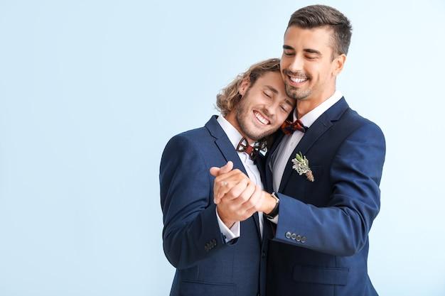 Ritratto di felice coppia gay il giorno delle nozze contro la superficie del colore