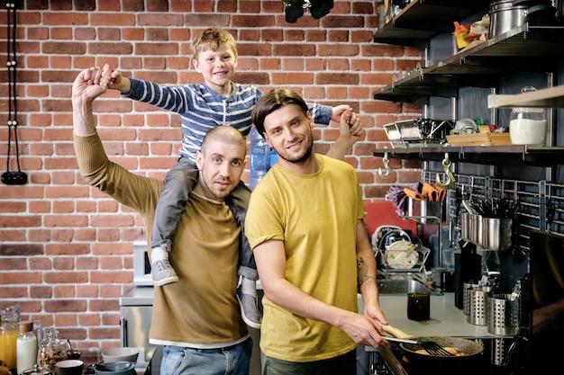 Ritratto di felice famiglia gay di due padri e ragazzino in piedi in cucina e cucinando la colazione