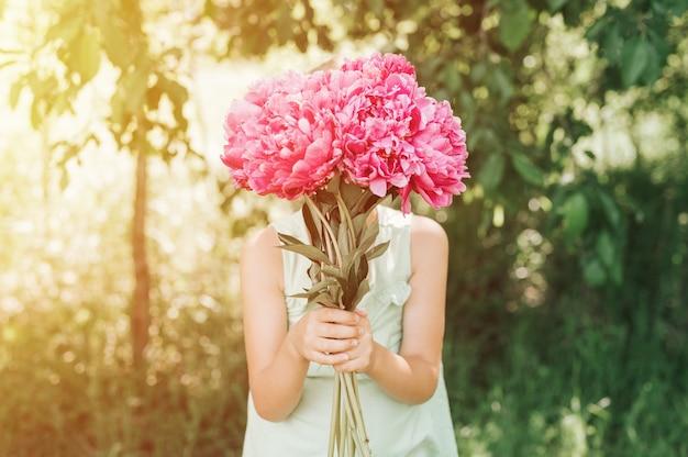 Ritratto di una ragazza felice con in mano un mazzo di fiori di peonia rosa in fiore
