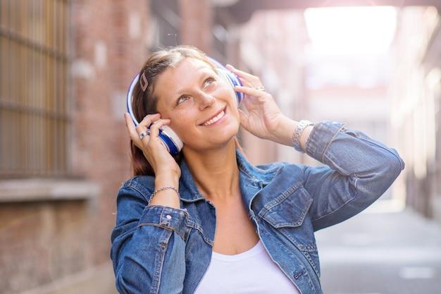 Ritratto di una ragazza felice ascoltando musica con cuffie wireless in strada