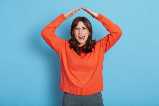 Ritratto di ragazza felice in maglietta arancione sentirsi al sicuro, fiducioso sotto casa