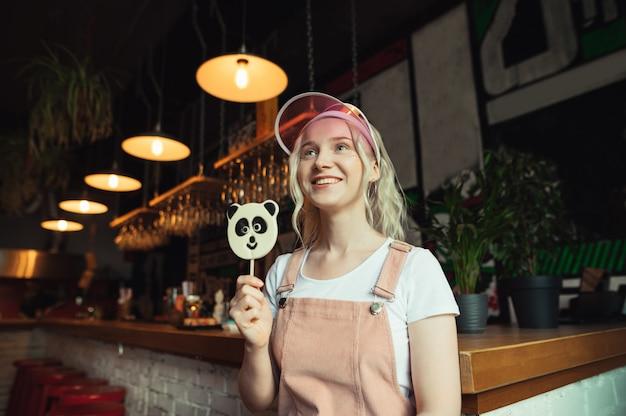 Ritratto di ragazza felice in abito rosa e lecca-lecca in mano