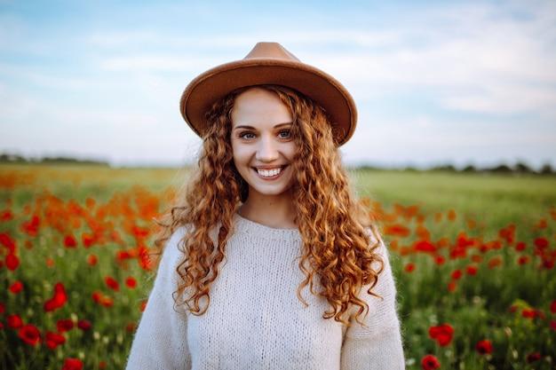 Ritratto di una ragazza felice in un campo di papaveri