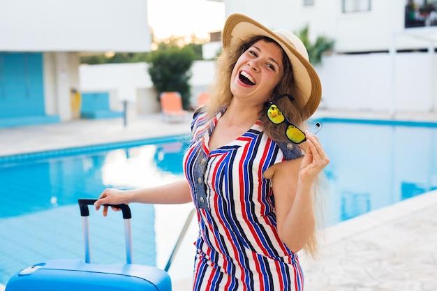 Ritratto di ragazza felice durante le vacanze estive contro la piscina, vestito a righe vestito e occhiali da sole.