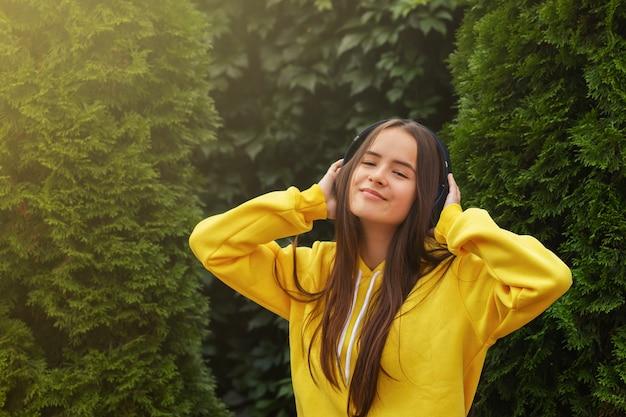 Ritratto di una ragazza felice in cuffie wireless in estate sullo sfondo di verdi alberi di natale