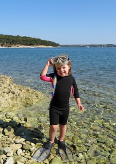 Ritratto di ragazza felice con muta, maschere e boccagli al mare