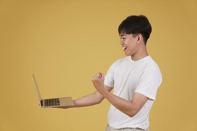 Il ritratto del giovane asiatico allegro di gioia felice felice si è vestito casualmente che tiene il computer portatile che fa il gesto del vincitore del pugno isolato