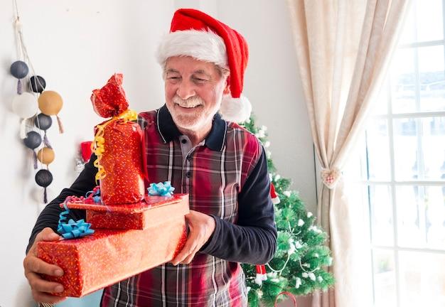 Ritratto di un nonno felice con la barba bianca che tiene molti regali di natale per la famiglia - buon natale a casa per un anziano pensionato che si gode le vacanze