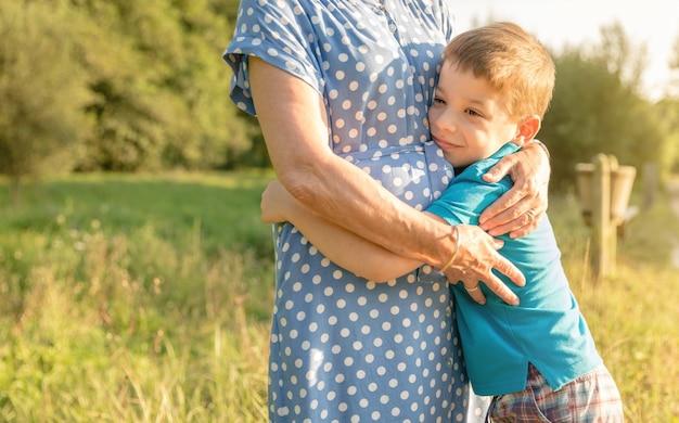 Ritratto di un nipote felice che abbraccia la nonna su uno sfondo naturale all'aperto