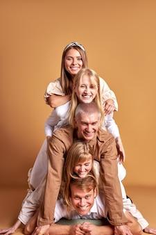Ritratto di felice gruppo di giovani caucasici divertendosi in studio con sfondo marrone
