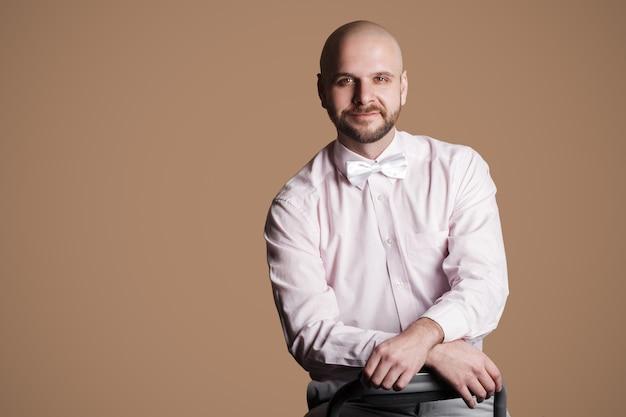 Ritratto di uomo calvo barbuto bello felice in camicia rosa chiaro e fiocco bianco, seduto su una sedia e guardando la fotocamera con sorriso e faccia soddisfatta. girato in studio al coperto, isolato su sfondo marrone.