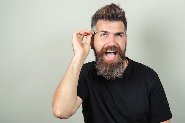 Ritratto di uomo barbuto bello felice che coglie le sopracciglia, su sfondo grigio, primo piano. salone di bellezza. concept beauty e trendy