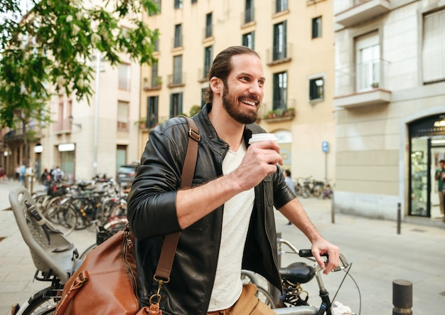 Ritratto di felice uomo bello anni '30 indossa giacca di pelle avendo pausa caffè sulla strada della città, dopo aver guidato la bicicletta