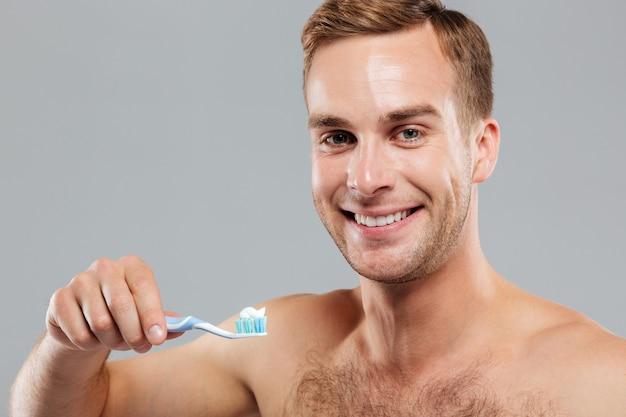 Ritratto di un bell'uomo felice che tiene lo spazzolino da denti isolato sul muro grigio