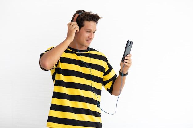 Ritratto felice uomo creativo ispanico che ascolta musica online sul telefono cellulare in piedi isolato su sfondo bianco