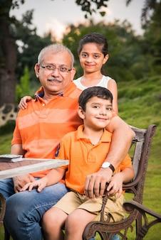 Ritratto di happy indian asian kids e nonno seduti su una sedia a sdraio