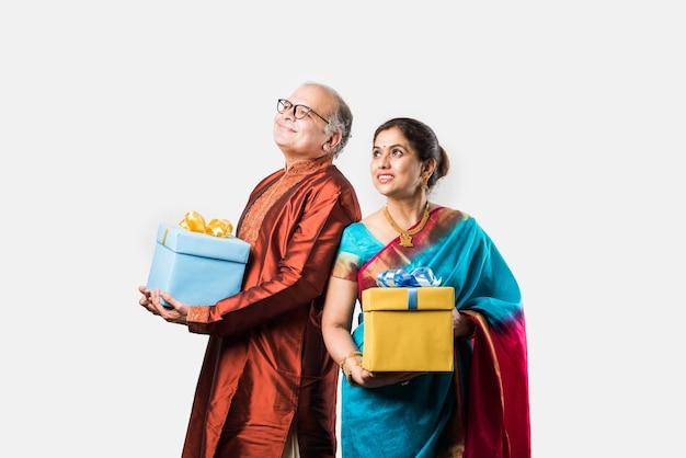 Ritratto di felice indiano asiatico senior o coppia di pensionati che tiene scatole regalo, isolate su sfondo bianco white