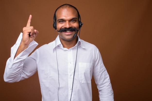 Ritratto di uomo d'affari indiano felice con i baffi come rappresentante del call center