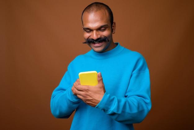 Ritratto di uomo indiano felice con i baffi utilizzando il telefono