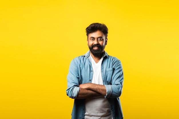 Ritratto di giovane uomo barbuto indiano felice con le braccia incrociate su giallo