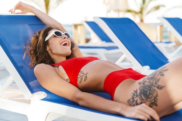 Ritratto di donna gioiosa felice in occhiali da sole che sorride mentre giaceva su una sedia a sdraio in una lussuosa spiaggia soleggiata
