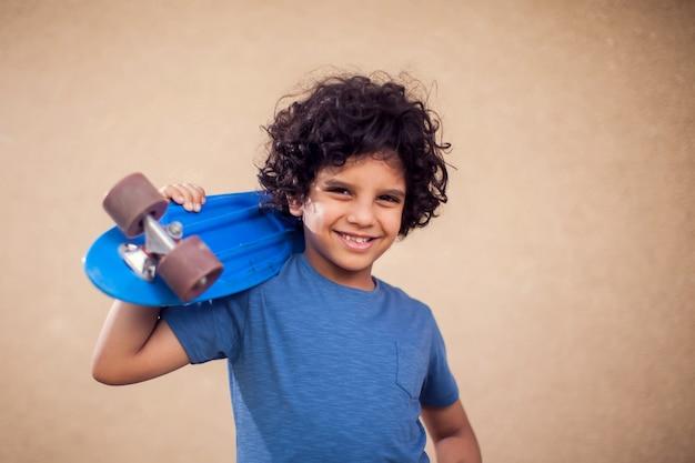 Ritratto di ragazzo felice bambino con i capelli ricci tenendo skateboard. concetto di bambini, tempo libero e stile di vita