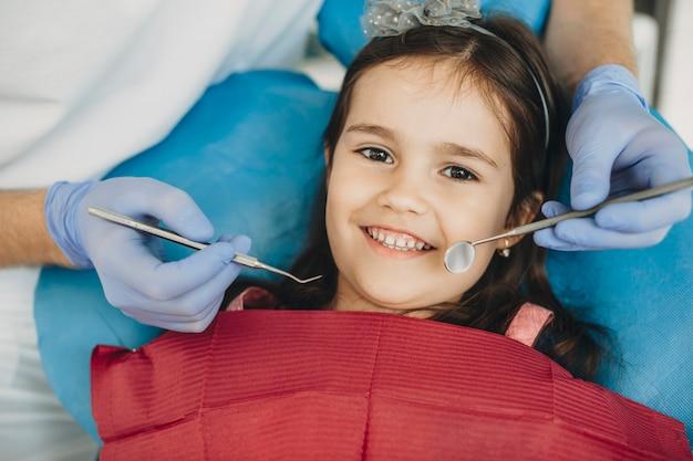 Ritratto di un bambino felice che sorride dopo la chirurgia dei denti. bambina adorabile che guarda l'obbiettivo che sorride dopo l'esame dei denti da un dentista pediatrico.