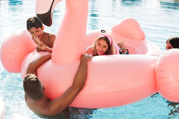 Ritratto di bambini felici e genitori che nuotano in piscina con anello di gomma rosa, fuori dall'hotel nella località termale