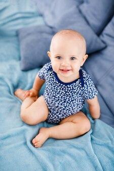 Ritratto di bambino che ride felice con gli occhi azzurri, in camicia blu, seduto sul divano.