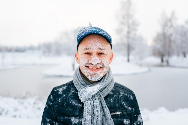 Ritratto di un uomo che ride felice con la neve sul suo viso in piedi all'aperto in una giornata invernale nevoso in natura.