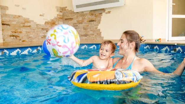 Ritratto di un bambino che ride felice con una giovane madre che gioca con un pallone da spiaggia gonfiabile colorato in piscina al resort estivo dell'hotel