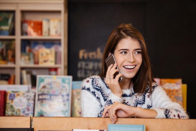 Ritratto di una donna che ride felice che parla al cellulare mentre è seduta in biblioteca