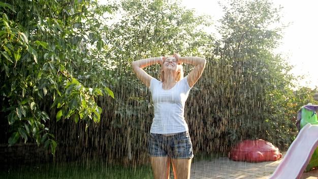 Ritratto di giovane donna che ride felice con i capelli lunghi in vestiti bagnati che ballano sotto la pioggia calda in giardino. la famiglia gioca e si diverte all'aperto in estate