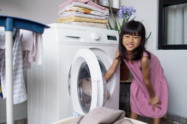 Ritratto di felice bambina asiatica facendo il bucato a casa