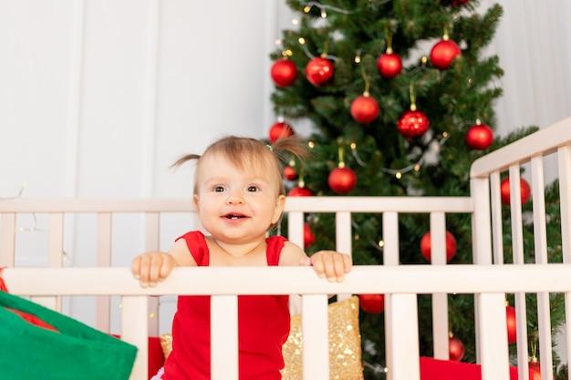 Ritratto di un piccolo bambino felice sei mesi in una culla a casa dall'albero di natale, capodanno e concetto di vacanza