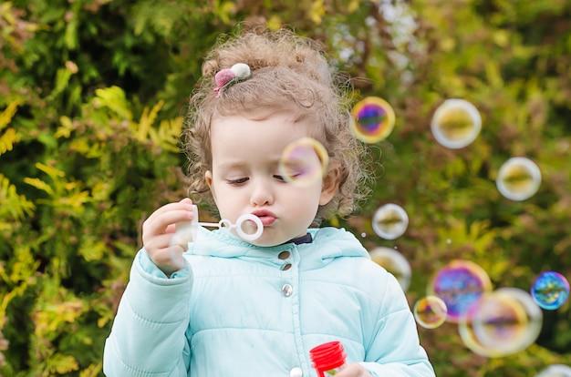 Ritratto di piccola bella ragazza felice che spegne le bolle di sapone sulla natura. il tempo libero dei bambini. divertenti giochi all'aperto