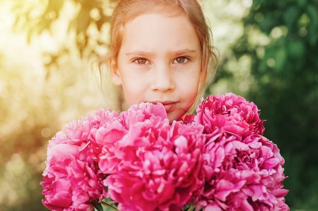 Ritratto di una felice bambina caucasica di sette anni, tiene in mano un mazzo di peonia rosa