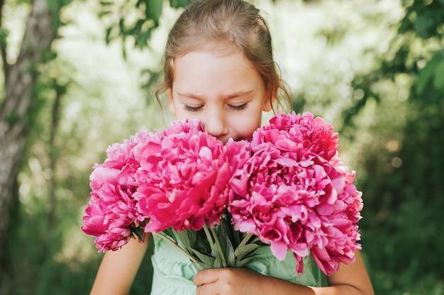 Ritratto di una felice bambina di sette anni caucasica, tiene in mano e odora e si diverte