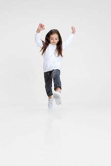 Ritratto del bambino felice della bambina che salta isolato sopra il fondo bianco dello studio