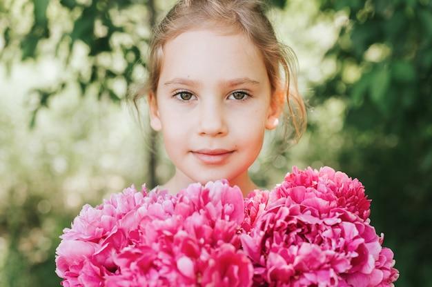 Ritratto di una bambina felice, tiene in mano un mazzo di fiori di peonia rosa in piena fioritura