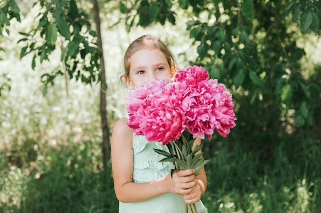 Il ritratto di una bambina felice tiene tra le mani un mazzo di fiori di peonia rosa in piena fioritura