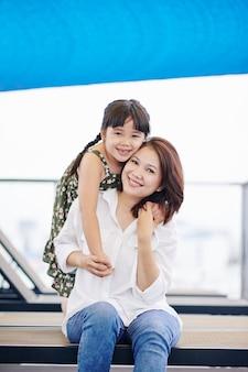 Ritratto di bambina felice che abbraccia la sua bella madre da dietro