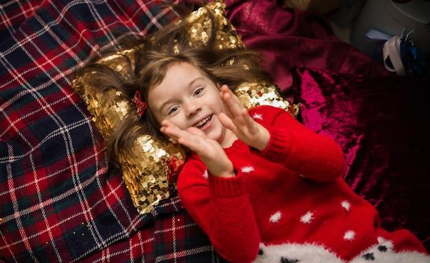 Ritratto di una bambina felice sdraiata e battendo le mani